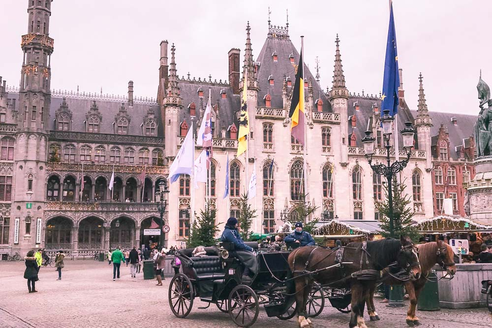 Bruges, market square, horse drawn carriages